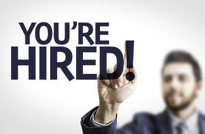 Business man pointing to transparent board with text You're Hired!